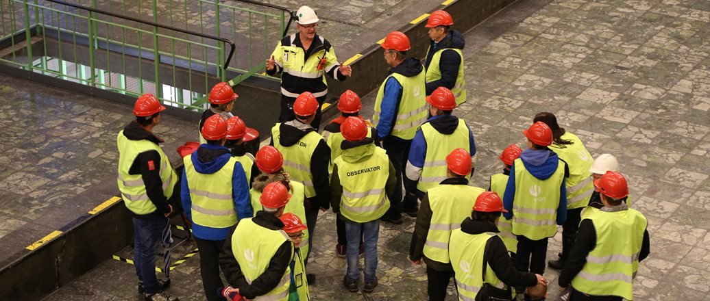 group of people in hard hats and yellow reflective vests