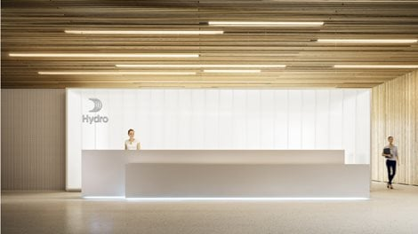 a large, well lit and airy reception. Wooden ceieling, white floor, wall and desks. Receptionist in a white top.