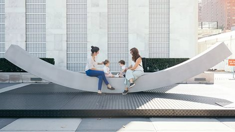 On the gently inwards sloping aluminium peace bench, two young mothers hold toddlers who play together.