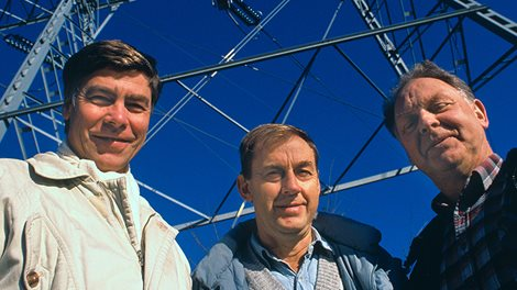 three men in front of a power mast